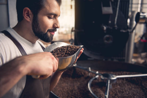 cheerful worker enjoying beans aroma - annusare foto e immagini stock