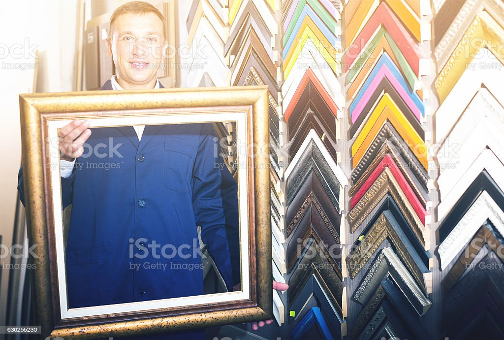 Cheerful Workman Holding Wooden Picture Framing Moulding Stock Photo