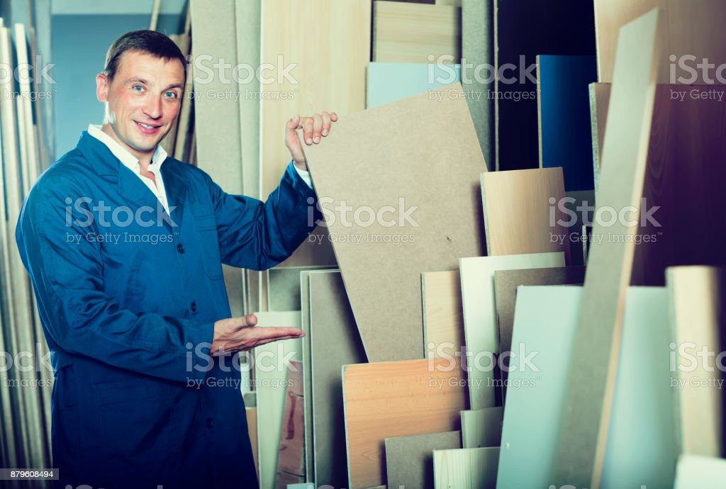 Cheerful workman standing with plywood pieces stock photo