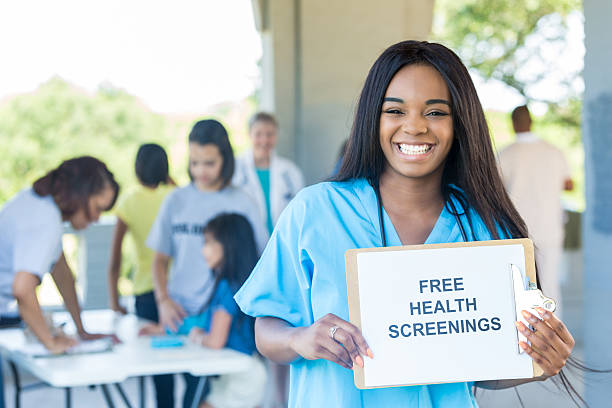 Cheerful young African American nurse promotes health fair Confident African American female nurse holds 'Free Health Screenings' sign to promote health expo. Patients and doctors are in the background. film and television screening stock pictures, royalty-free photos & images