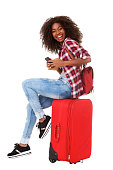 istock cheerful young african american woman sitting on suitcase and laughing over white background 992844244