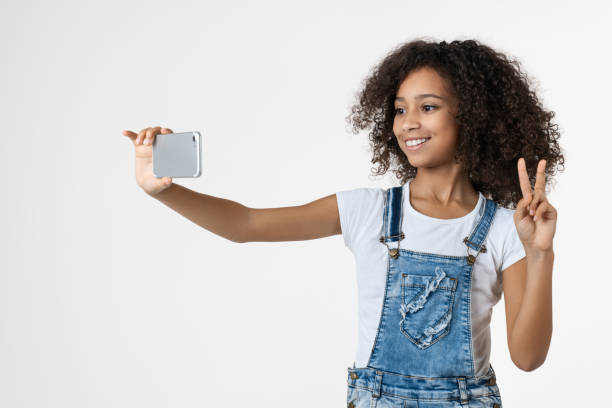 Cheerful young african girl kid using mobile phone taking selfie picture id1202500251?b=1&k=6&m=1202500251&s=612x612&w=0&h= kydnyk2fdwl0odg7zuu dxmg2wbobgvooxeojzxe9g=