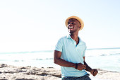 Portrait of cheerful young african man with hat enjoying at the beach on summer day