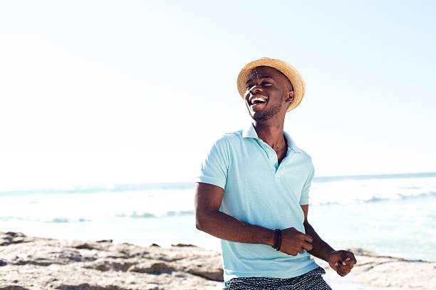 cheerful young african man enjoying at the beach - beach fashion stock photos and pictures