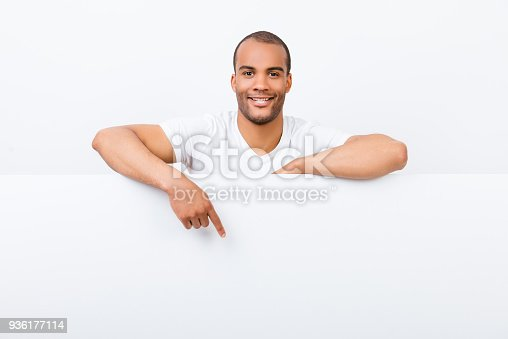 istock Cheerful young african man is standing behind the white blank banner and pointing down at a white copyspace, in casual wear 936177114