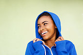 istock cheerful young african woman laughing against green wall 857924898