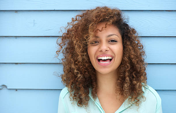 cheerful young african woman smiling - curly brown hair stockfoto's en -beelden