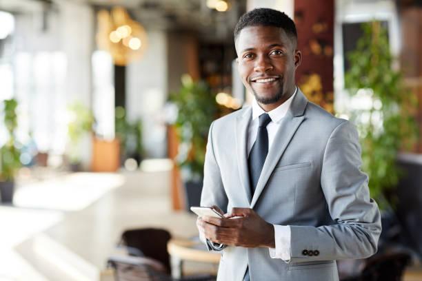 Fröhlicher junger afroamerikanischer Geschäftsmann mit Smartphone – Foto