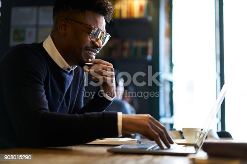 istock Cheerful young afro american male international student chatting with best friends via laptop computer connected to free wireless internet in cafe while preparing home tasks for lessons in university 908015290