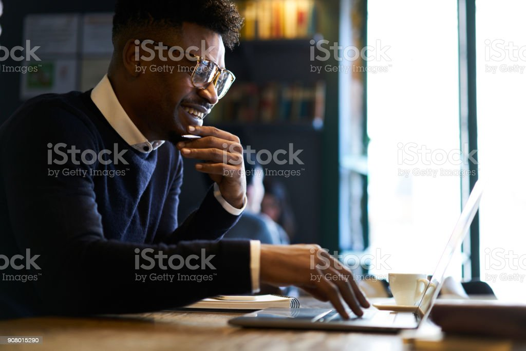 Cheerful young afro american male international student chatting with best friends via laptop computer connected to free wireless internet in cafe while preparing home tasks for lessons in university stock photo