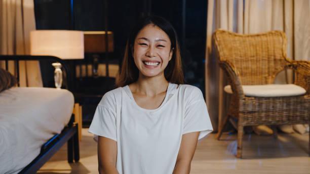 wanita muda asia yang ceria merasa tersenyum bahagia dan melihat kamera menggunakan telepon melakukan panggilan video langsung di ruang tamu di rumah malam. - live in dorm potret stok, foto, & gambar bebas royalti