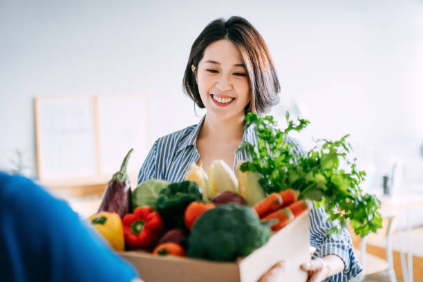 Cheerful young Asian woman receiving a box full of colourful and fresh organic groceries ordered online from delivery person at home
