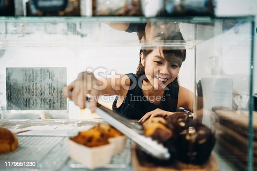 Cheerful young Asian woman working at a bakery and serving fresh bakery from the display cabinet