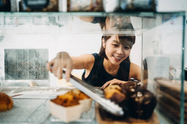 cheerful young asian woman working at a bakery and serving fresh bakery from the display cabinet - small business owner stock pictures, royalty-free photos & images