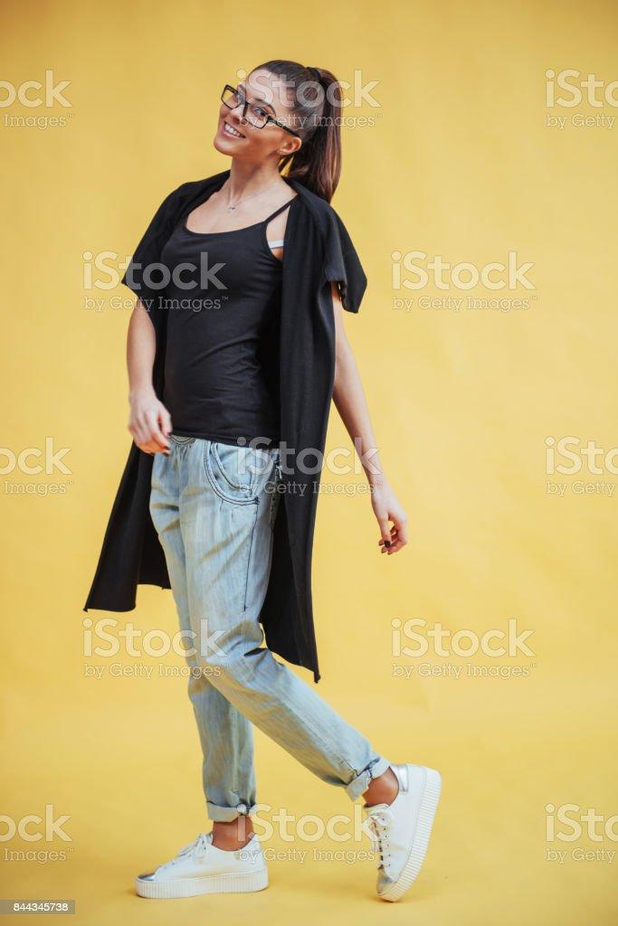 Bela mulher jovem alegre em copos, sobre um fundo amarelo no estúdio - foto de acervo