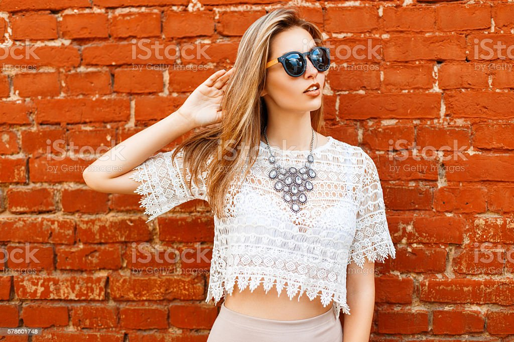 Cheerful young beautiful woman in sunglasses posing near brick wall – Foto