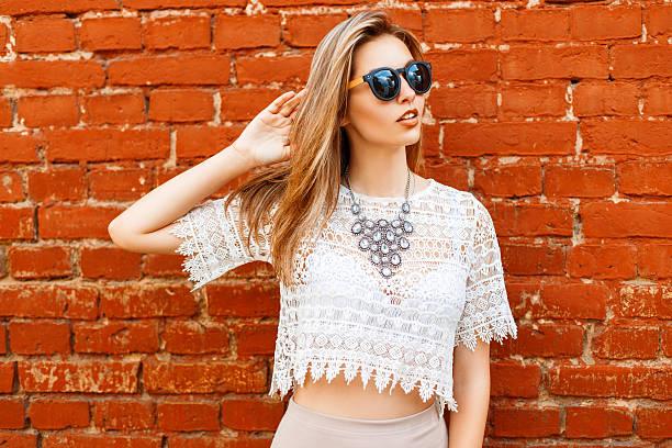 cheerful young beautiful woman in sunglasses posing near brick wall - koronka zdjęcia i obrazy z banku zdjęć
