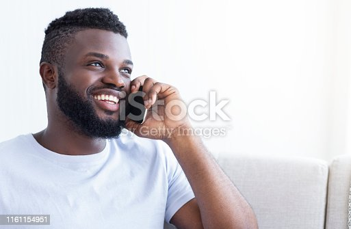 istock Cheerful young black man talking on smartphone 1161154951
