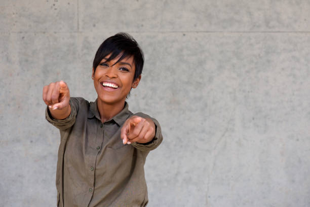 cheerful young black woman pointing fingers with copy space stock photo