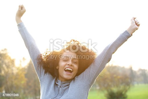 istock Cheerful young black woman smiling with arms raised 478801046