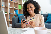 istock Cheerful young black woman using credit card at home 1277139299