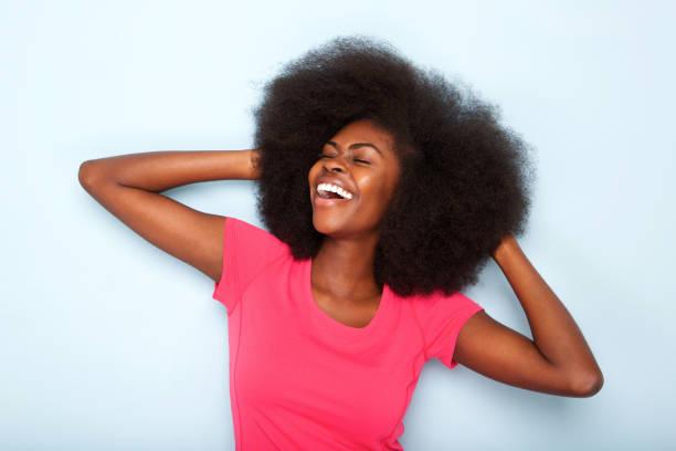 cheerful young black woman with hands behind head - афро стоковые фото и изображения