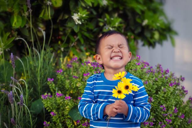 ein fröhlicher kleiner junge, der im frühjahr ein paar handgepflückte gelbe blüten hält und vor einem üppigen garten steht. - 2 3 jahre stock-fotos und bilder