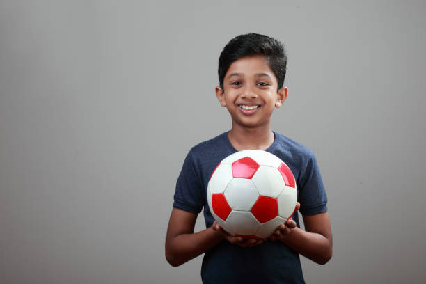 Cheerful young boy holds a ball in his hand stock photo