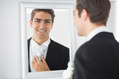 Cheerful young bridegroom standing in front of a mirror smiling at camera