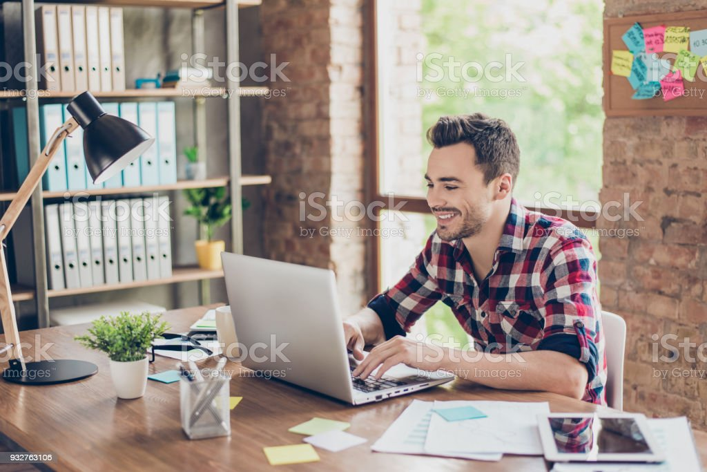Cheerful young brunet freelancer is smiling, typing on his laptop in nice modern work station at home, in casual smart wear stock photo
