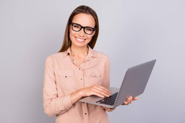 fröhliche junge brünette clever dame in einem beige hemd steht auf das pure grauen hintergrund mit laptop, lächeln, in die kamera schaut - damen shirts online stock-fotos und bilder