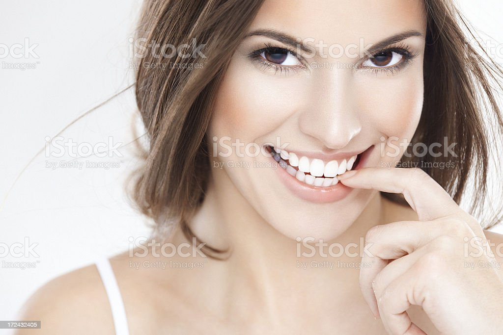 Cheerful young brunette woman with beautiful smile biting finger stock photo