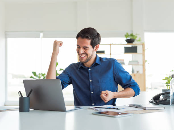 Cheerful young business man celebrating stock photo