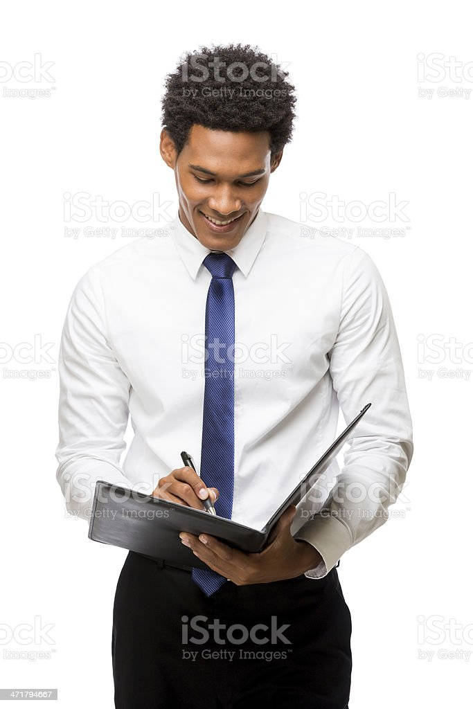 Cheerful young business man writing in folder stock photo
