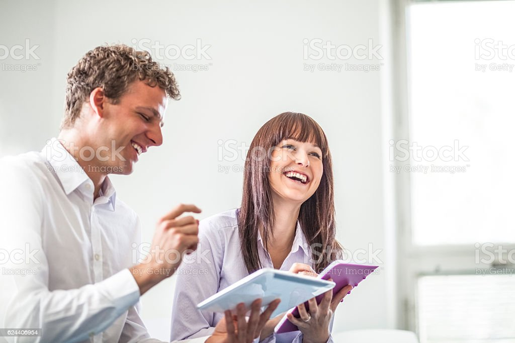 Cheerful young business people discussing together in office stock photo