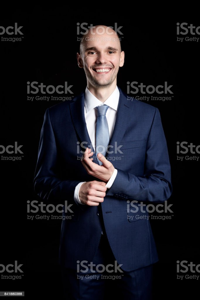 Cheerful Young Businessman Fixing Cuffs his Suit stock photo