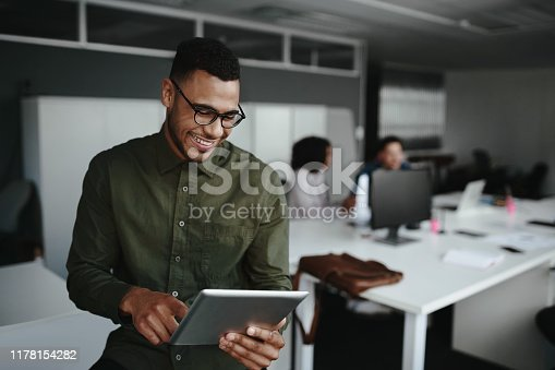 Successful smiling young man in office using digital tablet