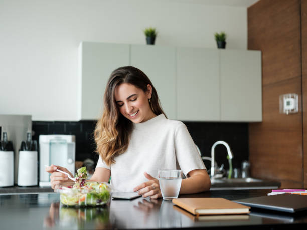 Cheerful young businesswoman eating salad in lunch room and using phone stock photo