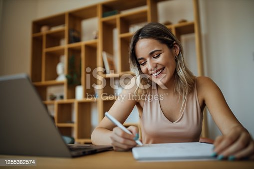 Cheerful young businesswoman taking notes, writing in note pad, portrait, close-up.
