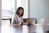 Beautiful young businesswoman smiles as she participates in a video conference with a colleague. She is using a laptop.