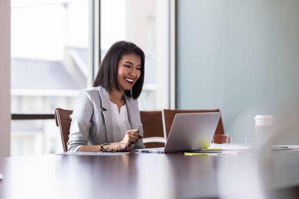 Cheerful young businesswoman video chats with colleague stock photo