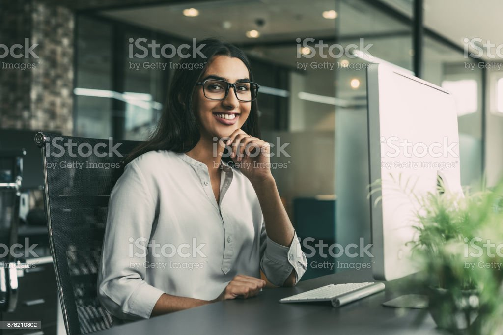 Cheerful young businesswoman working in office stock photo