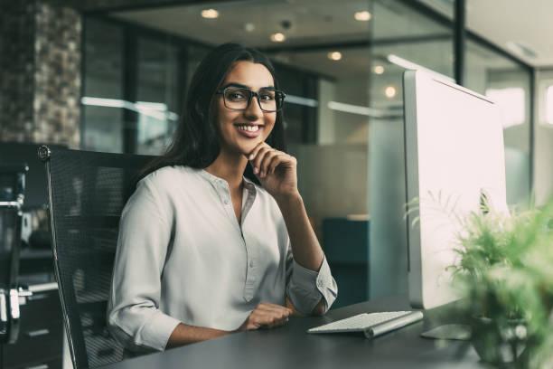 cheerful young businesswoman working in office - popolazione indiana foto e immagini stock