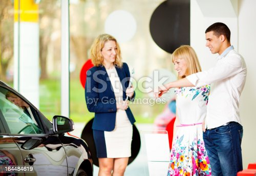 917259790istockphoto Cheerful Young Couple Buying Car. 164484619