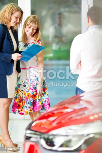 1178695243 istock photo Cheerful Young Couple Buying Car. 164602647