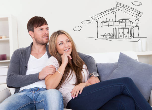 Cheerful young couple dreaming about the future Cheerful young couple dreaming about the future sitting at couch model home stock pictures, royalty-free photos & images