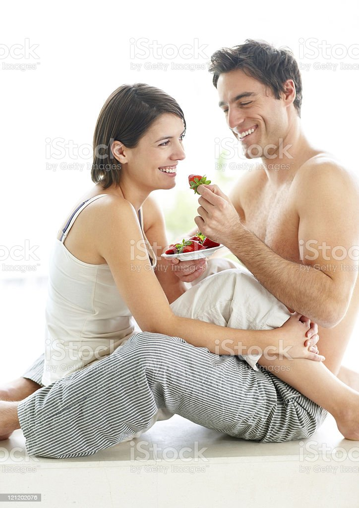 Cheerful young couple eating strawberries together royalty-free stock photo