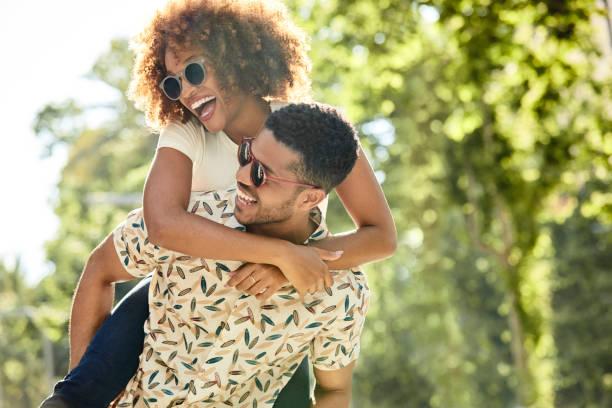 Fröhliches junges Paar genießt Huckepack-Fahrt – Foto