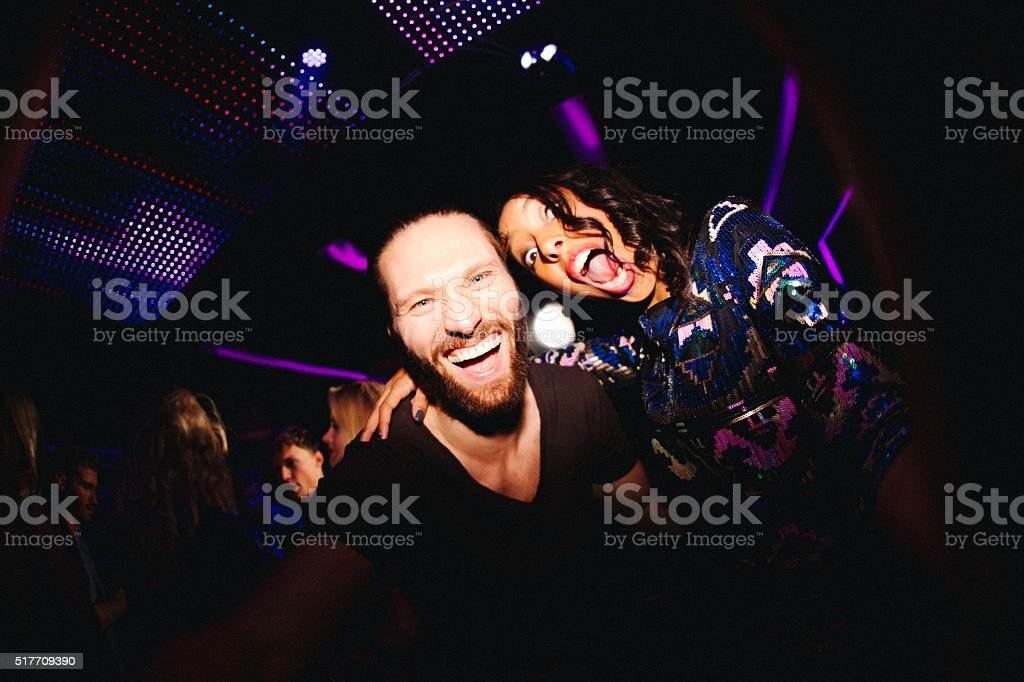 Cheerful young couple having fun with selfie at disco stock photo