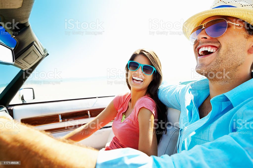 Cheerful young couple in a convertible car going for vacation stock photo